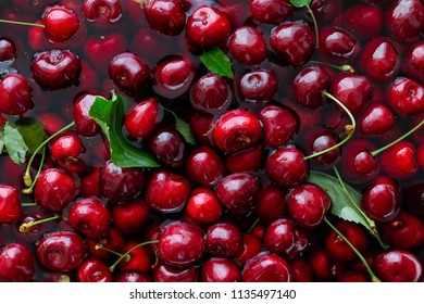 Background of freshly picked red cherries with leaves in water from above.