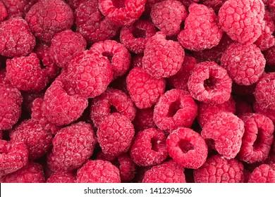 Background of frozen raspberries. Ripe raspberries with frosty freshness