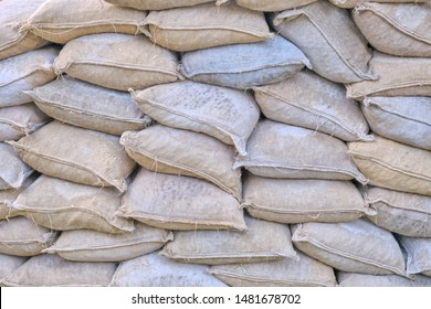 Background of full burlap dirty bags. Protective wall of sandbags. Piled sandbags for protection against natural disasters, texture.