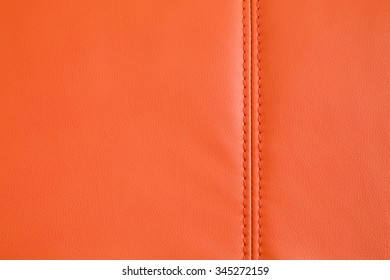 Background full frame texture of Orange artificial leather with a stitched seam on an upholstered settee or couch in an interior decorating concept.
