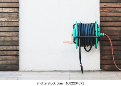 Background of a garden hose reel fixed on the wall. Blank wall on center with wooden boards decoration.