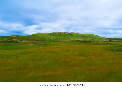 Background gently sloping hills with a green meadow foreground and dark stormy skies
