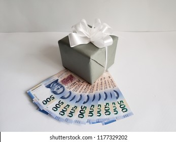 background with gift box and stacked mexican banknotes of 500 pesos