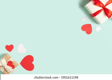 Background with gift and hearts with free space for text on pastel blue background. Valentines day concept. Mother's Day concept. Greetings. Copy space. Flat lay, top view.