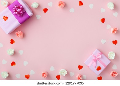 background of gifts with confetti hearts and roses, boxes wrapped in decorative paper on pastel colored pink background, top view, holiday concept and love