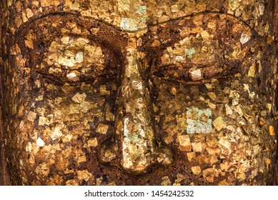 Background of Gilding to cover image Buddha with Shiny yellow leaf gold foil  to face of Buddha statue that Buddhist show to worship at the temple,Thailand