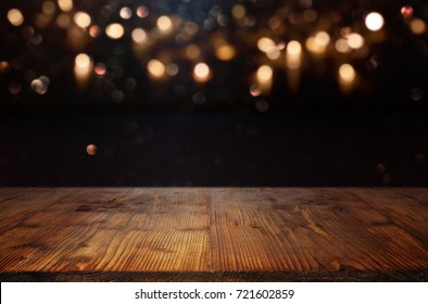 Background with golden bokeh and a empty wooden table  for a christmas decoration