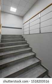 Background of gray staircase with wooden handrail in office building