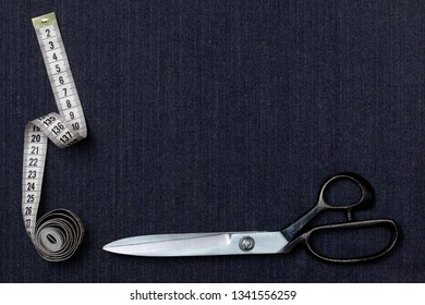 background gray woolen costume fabric closeup. scissors and measuring tape on the fabric. view from above