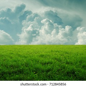 Background with green dense grass and beautiful storm clouds