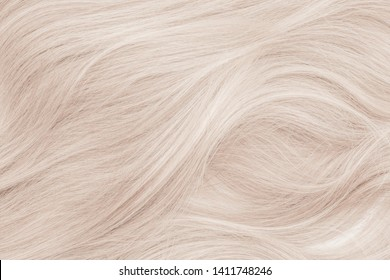 Background hair closeup. Female long blond hair close-up as a background. Beautifully laid wavy shiny curls. Hair coloring. Hairdressing procedures. Copy space with space for text.