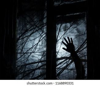 Background for Halloween party design. Silhouetted tree branches. Dark night. Hand of villain outside the window