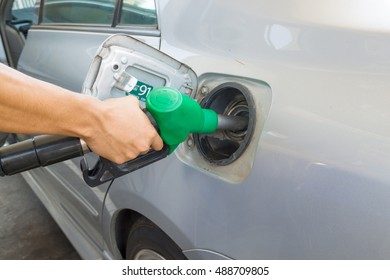 background of hand filling up car fuel, green energy