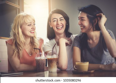 Background of a happy group of close friends chatting and talking over lunch in coffee shop. Beautiful pretty caucasian and asian women sitting together very enjoy and laughing with smile in holidays