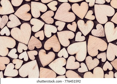 Background of hearts of different sizes close-up. A lot of decorative wooden hearts as a festive background.