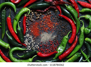 background with hot peppers. different kinds of pepper on a black background-fragrant, black pepper, white peas, jalapeno, chili, green, ground. spicy. Flatlay