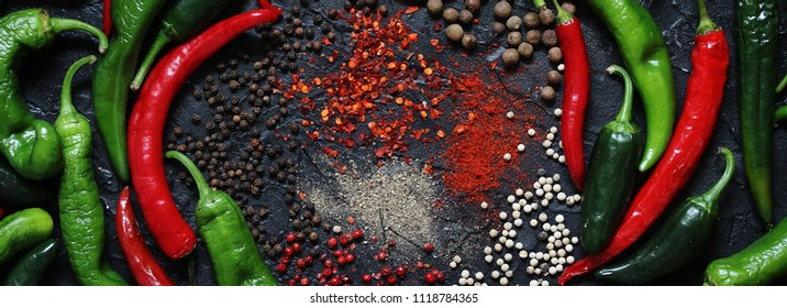 background with hot peppers. different kinds of pepper on a black background-fragrant, black pepper, white peas, jalapeno, chili, green, ground. spicy
