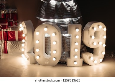 Background illuminated numbers of upcoming New Year 2019. Illuminated digits on the table around decorative handmade silver Christmas tree.