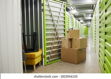 Background image of cardboard boxes stacked by open door of self storage unit, copy space
