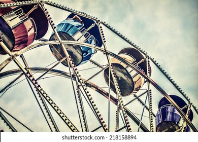 Background image of a close up low angle view of ferris wheel passenger cars high up against a cloudy sky at an amusement park.  Filtered for a retro, vintage look.