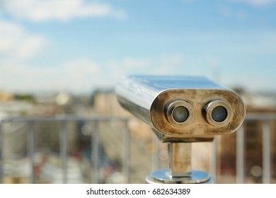 Background image of coin operated binoculars standing on rooftop viewing platform pointed over old European city