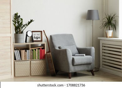 Background image of cozy reading nook in modern minimal interior, focus on grey armchair against white wall, copy space