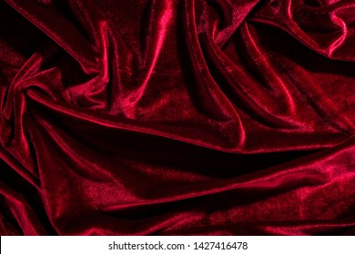 Background image of crumpled fabric. Red velvet