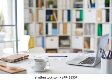 Background image of empty workplace in modern office, desk with laptop and office supplies on it