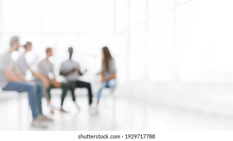 background image of a group of young people at a meeting in a conference room