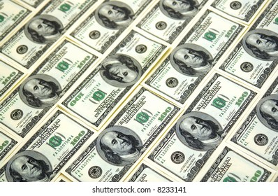 background image of hundred dollar bills, one is turned upside down, shot at an angle
