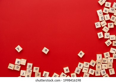 Background image The letters are scattered in disarray. English letters. wooden square letters on bright red background. Greeting card, ready-made layout, selective focus
