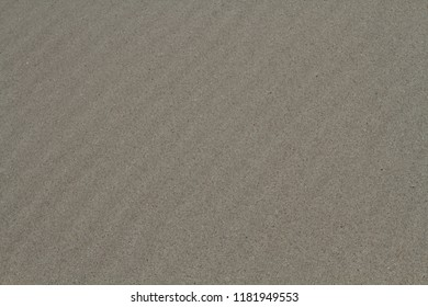 The background image of natural sea sand lies beautiful furrows. Background for a big board.