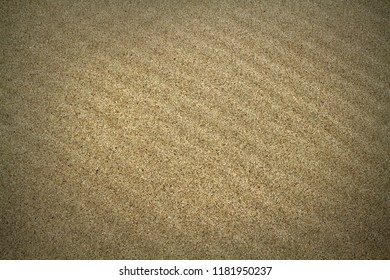 The background image of natural sea sand lies beautiful furrows. Background sand with vignetting.