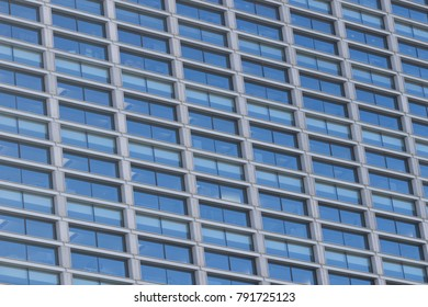 Background image of an office building facade full of glass windows.