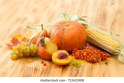 Background image of pumpkins, apples, pears, corn on the cob,grapes, mountain ash and autumn leaves on the wooden table. Place for text.