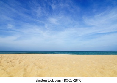 The background image of sand at the beach with sea and blue sky.