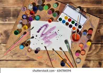 Background image showing interest in watercolor painting and art. A painted sheet of paper, surrounded by brushes, jars of watercolor paint and gouache, which lie on an old and stained wooden surface