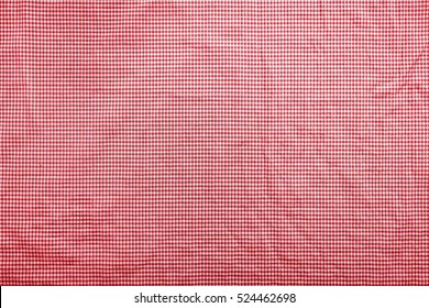 Background image with a slightly wrinkled red and white traditional italian checkered tablecloth
