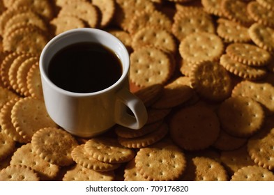 Background image of a small white cup of coffee and classic salty cracker on a brown wooden table with copyspace