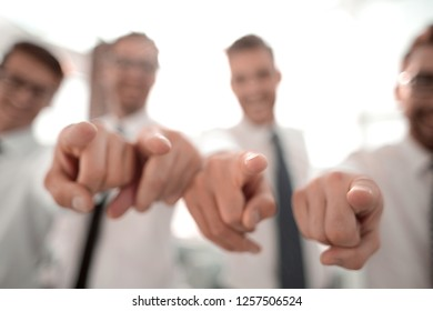 background image of a successful business team pointing to you