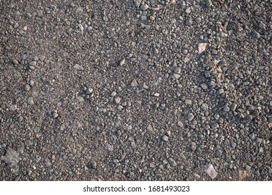 Background image of the surface covered with small gravel on the ground. Wallpaper. Substrate for text. Detailed texture of fine pebbles on the ground. The surface of the hiking trail. Top view.