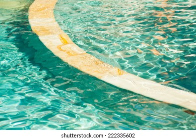 Background image of swimming pools with curved dividing wall.