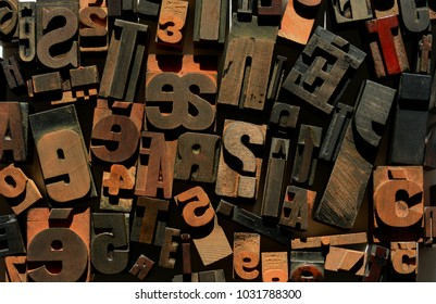 A background image of a variety of wooden alphabets, letterpress letters and numbers