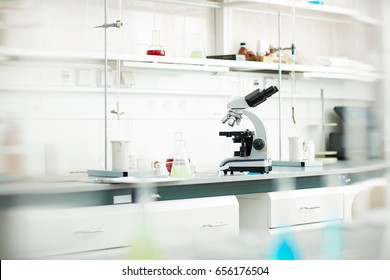 Background image of various equipment and microscope on table in empty laboratory
