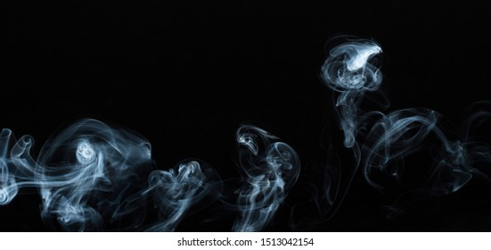 Background image of a wisp of smoke on a dark background. The texture of the flowing smoke. Graphic resources dark backdrop. Texura of white clouds of fog. Curls of smoke frozen in motion.
