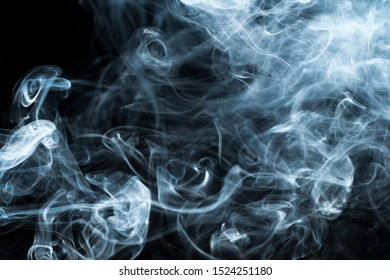 Background image of a wisp of smoke on a dark background. The texture of the flowing smoke. Frozen smoke on a dark background. Graphic resources dark backdrop. Curls of smoke frozen in motion.