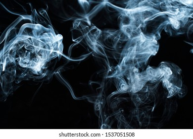 Background image of a wisp of smoke on a dark background. The texture of the flowing smoke. Frozen smoke on a dark background. Texura of white clouds of fog. Curls of smoke frozen in motion.