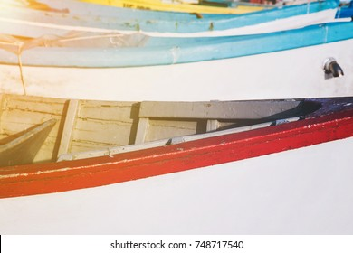 Background image of Wooden fishing boats in closeup with a blank area suitable for text, for example Name, Number, Town or Country with the glow of the sun in the corner