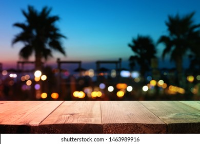 background Image of wooden table in front of abstract blurred tropical palms at sunset lights