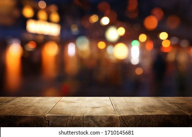 background Image of wooden table in front of abstract blurred restaurant lights